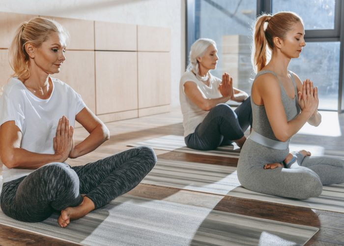 three women of different ages practicing yoga
