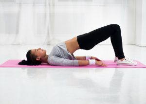 woman on yoga mat doing bridge pose