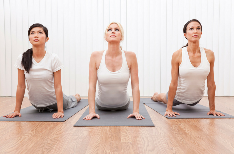 three women dressed in white doing yoga cobra pose