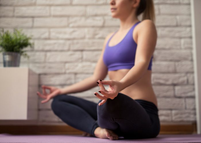 woman sat on yoga mat doing yoga meditative pose