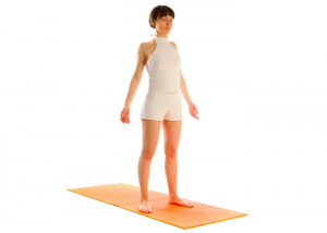 woman standing upright on yoga mat performing mountain pose