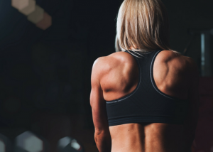 back view of a woman with a very muscular back in a sports bra