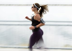 woman running outdoors while listening to music with earphones