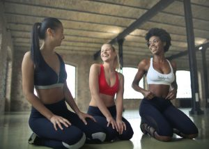 three women in workout clothes kneeling on the floor and laughing