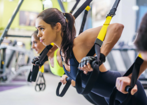 woman working out on TRX machine as part of a HIIT workout
