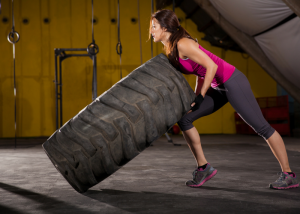 a woman in fitness gear lifting a large rubber tire
