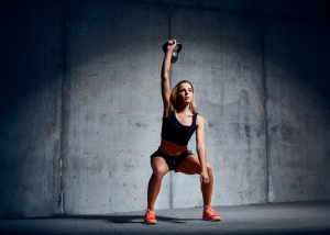 a woman squatting and holding a kettlebell weight above her head