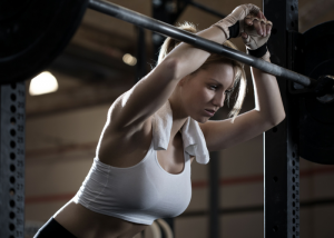 a woman in white sports bra leaning forward on a weightlifting bar