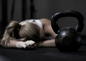an exhausted woman resting on the floor with a kettlebell in the foreground