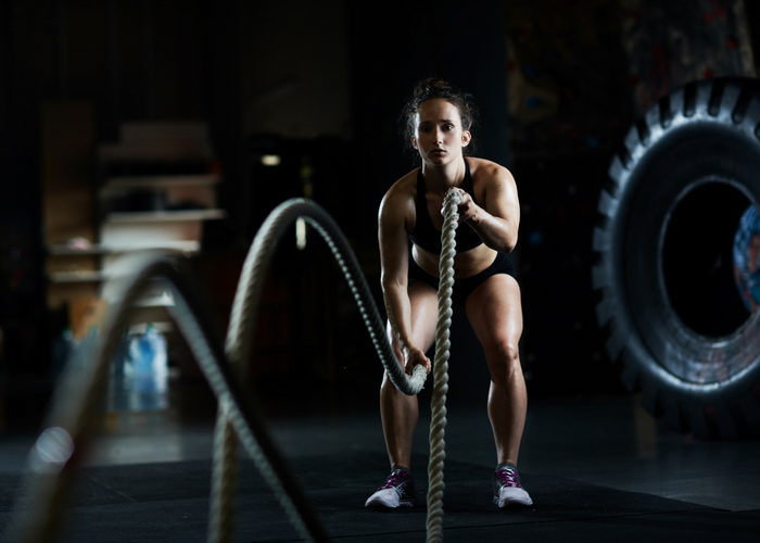 a fit woman doing battle rope exercises in a dark gym