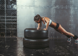woman doing elevated push ups on two stacked rubber tires