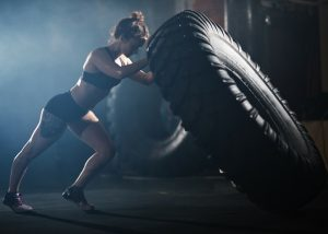 woman lifting a large tire in fitness workout