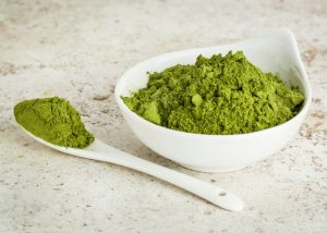 superfood moringa powder in a bowl and a spoonful beside it