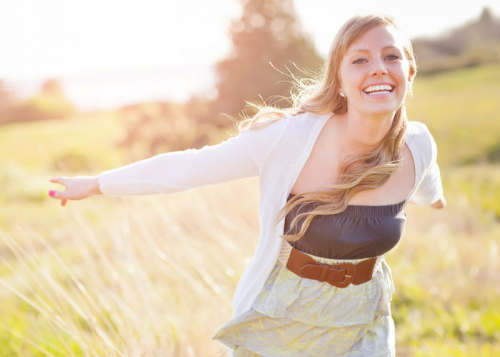 a smiling and confident woman with outstretched arms in a field