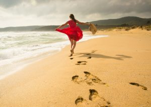 happy woman in red dress walking on a beach
