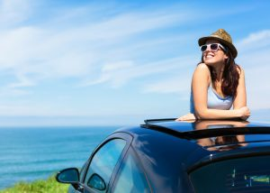 confident woman in a hat and sunglasses leaning out of her car's roof smiling