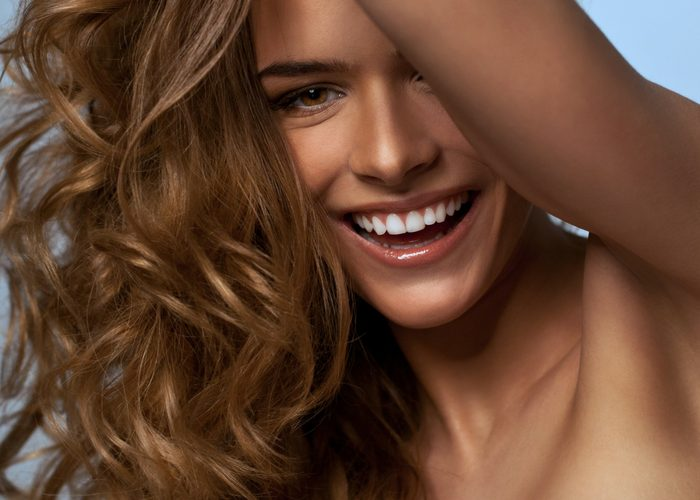 close up of a smiling confident woman with curly hair and tan skin