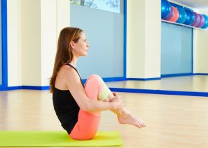 a woman sat on a pilates mat with her knees to her chest performing a pilates ball roll