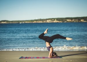a woman on a beach performing a yoga pose on her head