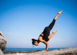 a woman performing a complex yoga pose on rocks