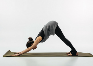 a woman doing the downward facing dog pose on a yoga mat