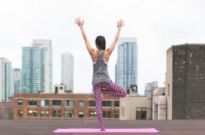 Woman on a rooftop standing on a pink yoga mat in a yoga pose