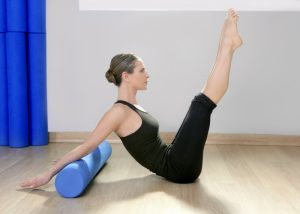 a woman using a pilates foam roller in her workout