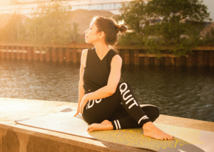 a woman performing a yoga pose by a river with the sun in her face