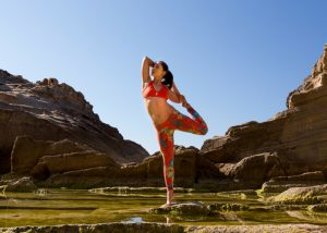 a woman standing on one leg on a rock doing a yoga pose