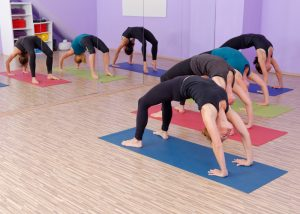 a group of women doing back bridge yoga poses on yoga mats