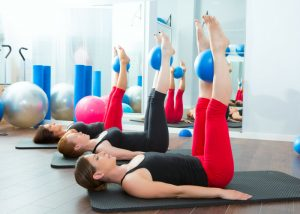 women in a pilates class lying on pilates mats and holding a ball between their legs