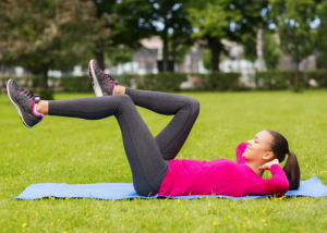 a young woman laid on a pilates mat outdoors performing pilates leg circles