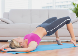 a woman lying on a pilates mat with her pelvis raised in the air