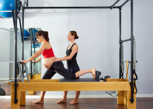 a pregnant woman doing a pilates workout with her instructor