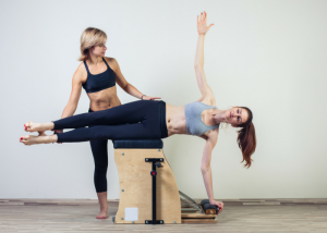 a woman using the pilates wunda chair machine with an instructor guiding her
