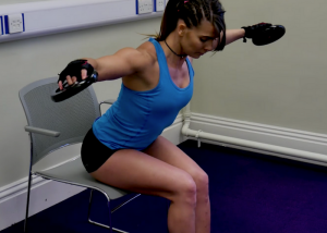 woman seated in a chair with her arms out at each side doing dumbbell exercises