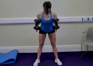 woman holding dumbbells doing standing triceps extensions
