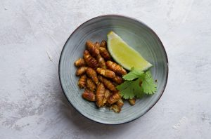 Bowl of edible insects with a lime wedge on a gray background