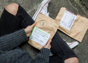 a girl holding onto packets of edible insect powders