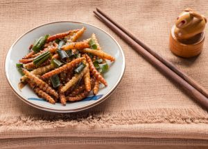 a small plate of fried mealworms with chopsticks on a table