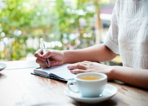 a woman writing in her diary with a cup of tea at the side