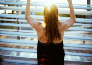 a fit women doing pull ups outdoors
