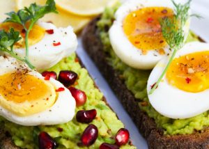 hard boiled eggs on avocado toast with pomegranate seeds