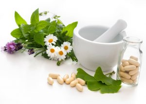 ginkgo biloba leaves, herbs, flowers, pestle and mortar as well as supplement capsules on a table