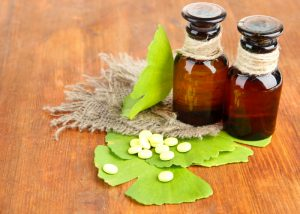 two small brown bottles and some pills on ginkgo biloba leaves