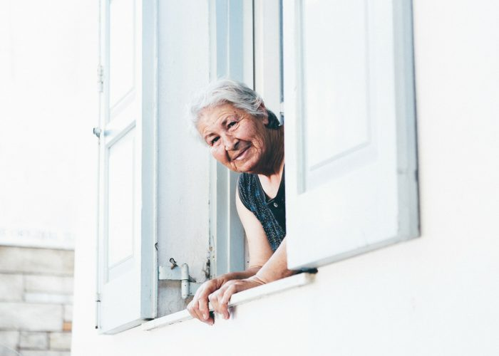 old woman looking out her window