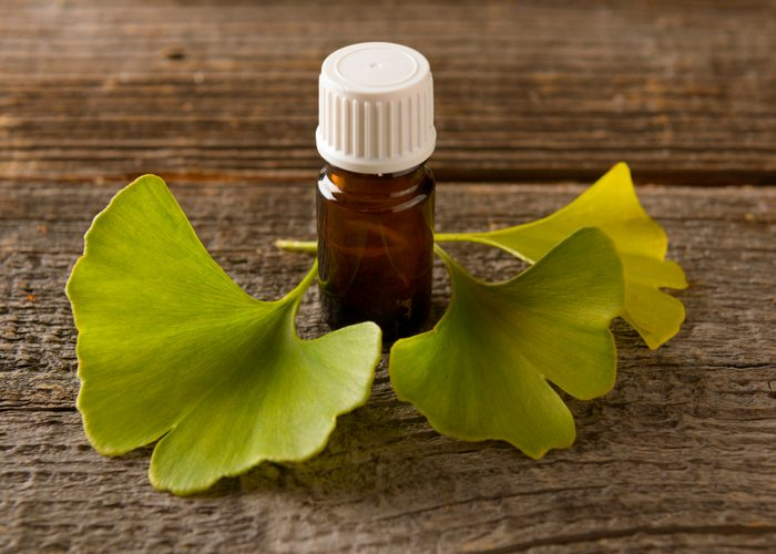 ginkgo biloba leaves and a bottle of extract on a wooden table