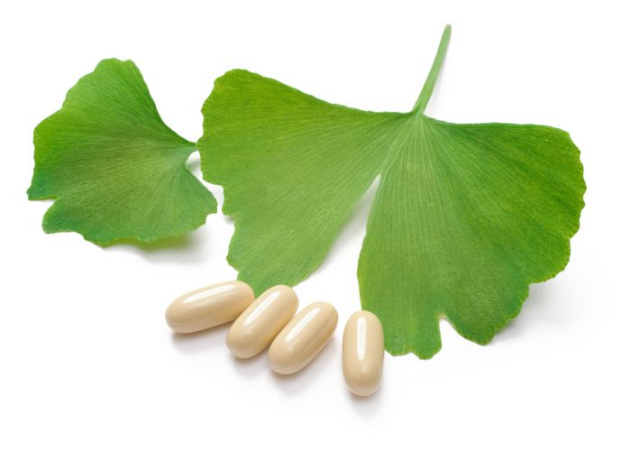 ginkgo biloba supplement pills and leaves on a white surface