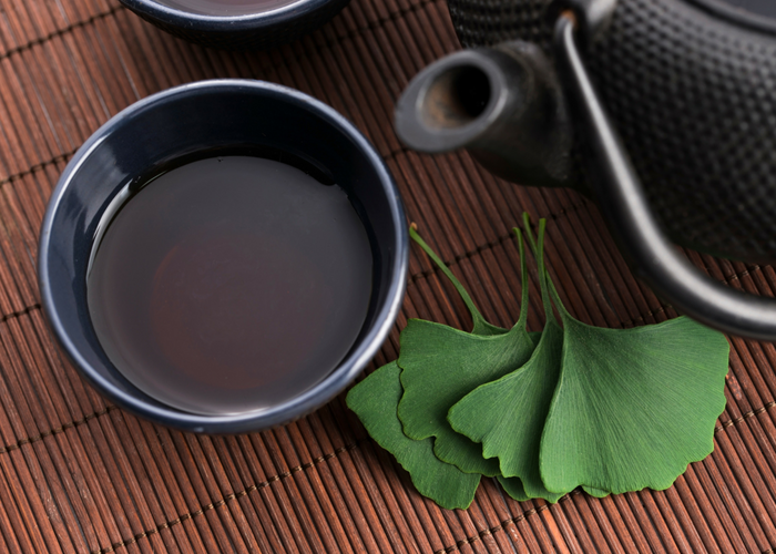 ginkgo biloba tea in a cup and leaves on a table