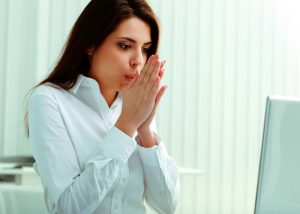a woman blowing on her hands to keep warm in the office